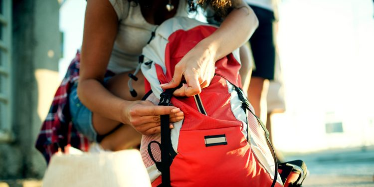 Woman doing up buckles on backpack