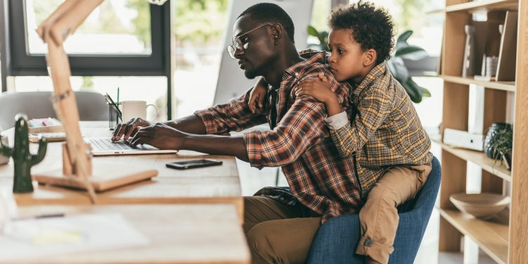 Side view of african-american father and son using laptop while sitting together in office