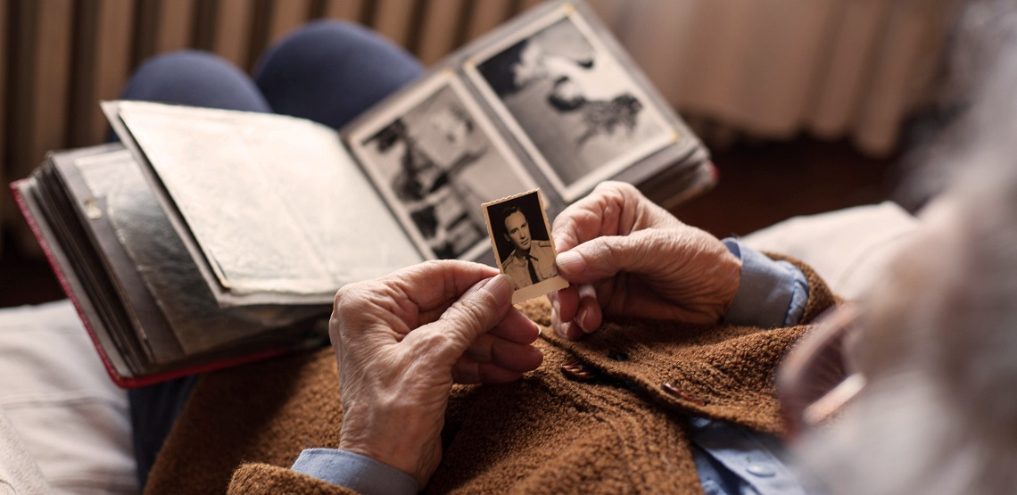 Over-the-shoulder view of a senior adult woman looking at an old photo of her husband