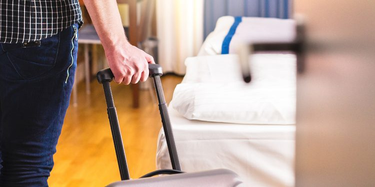 Someone with suitcase entering a hotel room