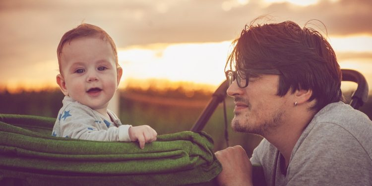 Father and baby in stroller outdoors at sunset