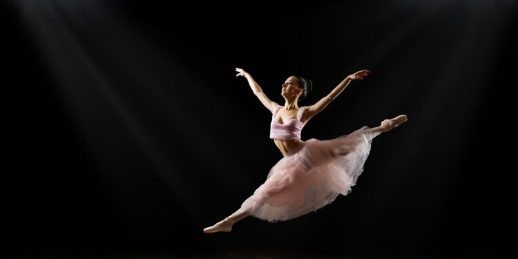 Young ballerina leaping against a black backdrop