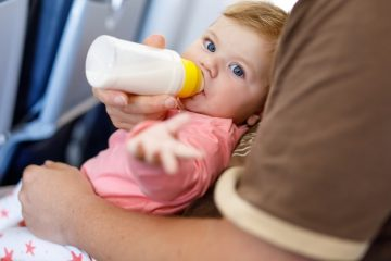 Baby girl drinking a bottle of milk on an airplane
