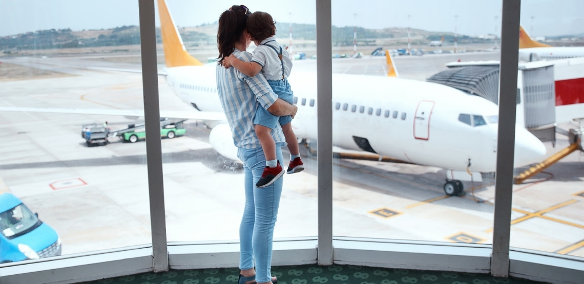mom holding older baby looking out the window of an airport