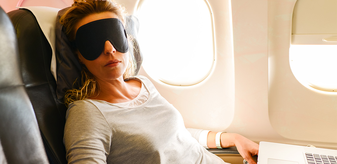 Woman with a sleeping mask and a laptop in front of her on a plane