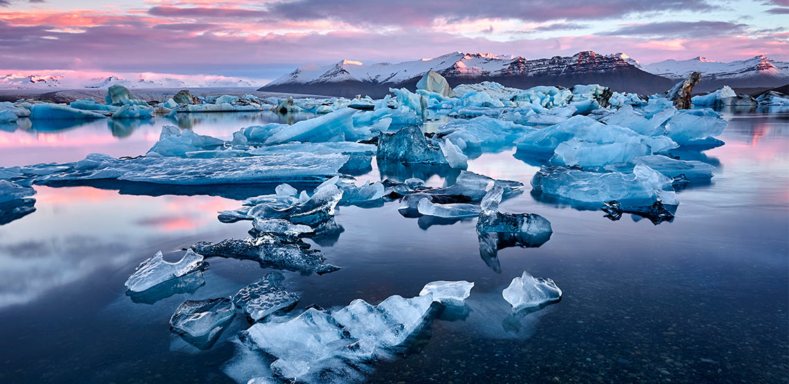 Ice and icebergs floating in water with mountains in background