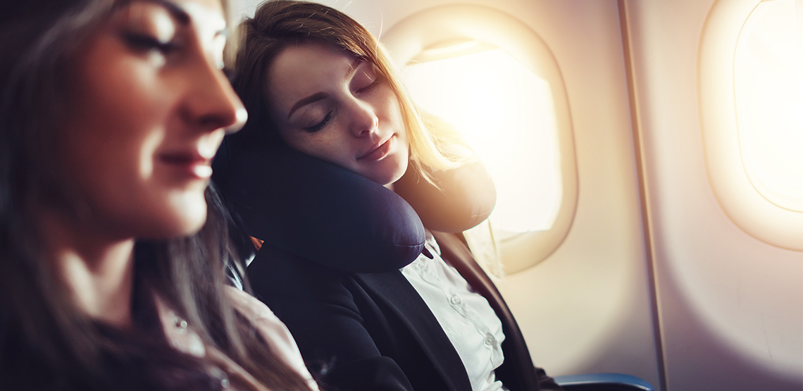 Two women sleeping on a plane, one with a neck pillow.