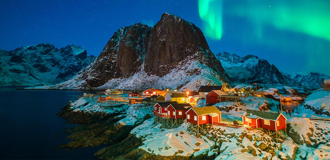 Small town with mountains in background and Northern Lights in sky