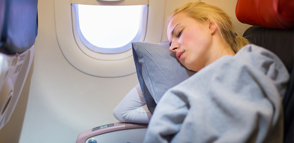 Woman sleeping on a plane with a pillow and blanket