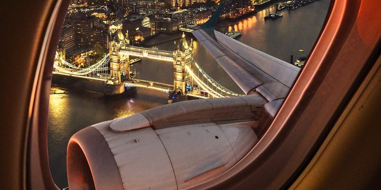 View out a plane window of London Bridge lit up at night