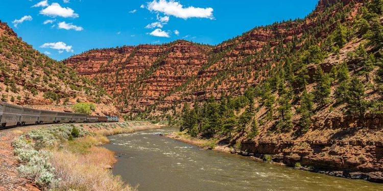Train traveling along river in Colorado