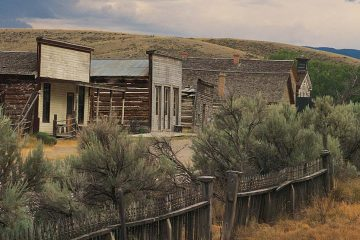 Old storefronts along dirt road with fence
