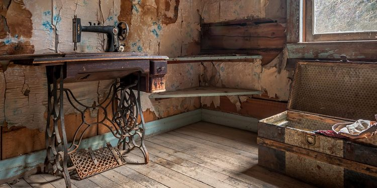 Sewing machine table and chest in dilapidated room