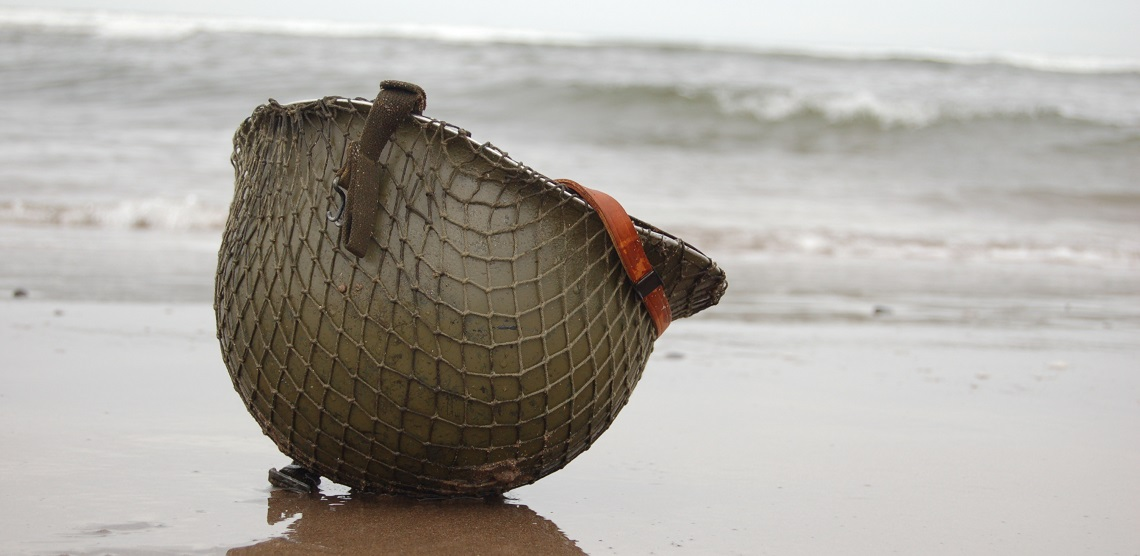 A brown helmet rests on the wet sand while waves lap behind it.