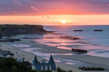 The sun sets purple and orange over a temporary, World War II-era harbor located in Arromanches-les-Bains, France.