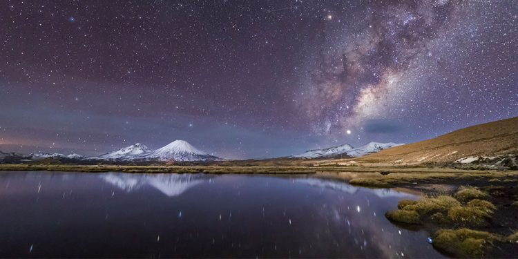 Starry sky over lake and snow-capped mountains