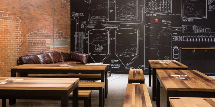 Wooden tables with a couch and drawings of beer barrels on chalkboard