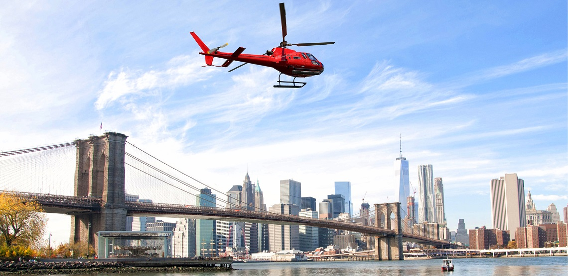 A red helicopter speeds over the Brooklyn Bridge, the skyscrapers of Manhattan visible in the background.