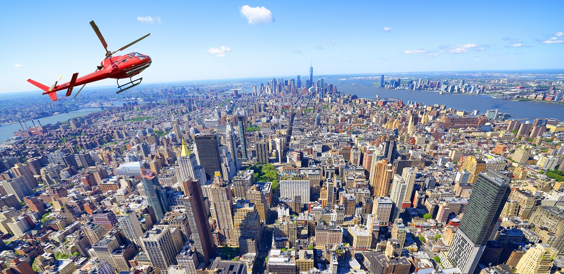 A red helicopter banks over New York's Manhattan neighborhood, famous high rises laid out below it.
