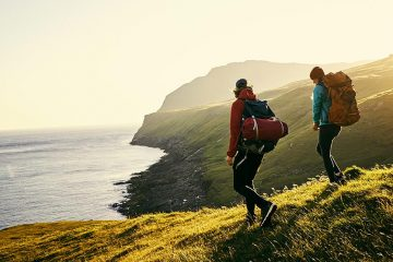 Two people wearing backpacks hiking along the coast