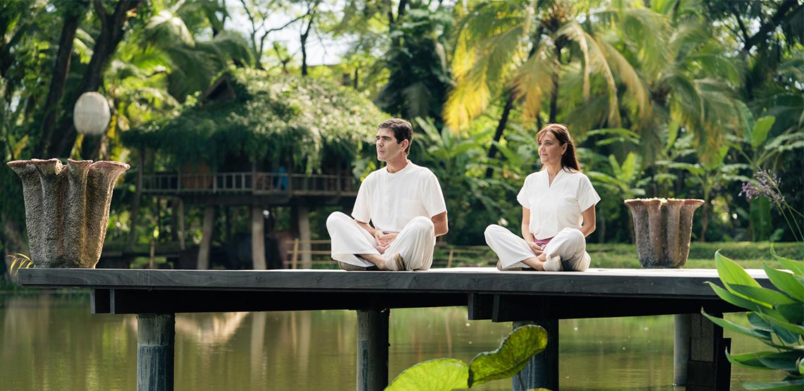 Two people sitting on dock over water with jungle in background
