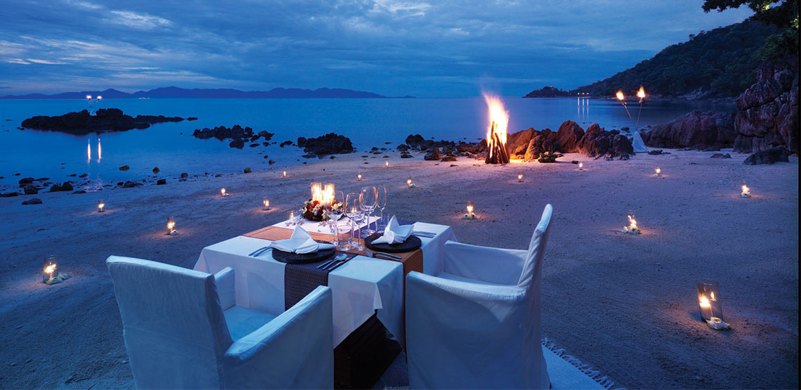 Table with plates on a beach with bonfire