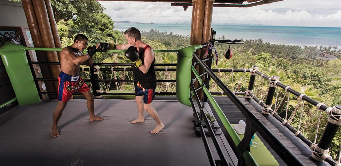 Two men kickboxing on platform overlooking jungle and ocean.