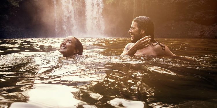 Man and woman swimming in river with waterfalls in background