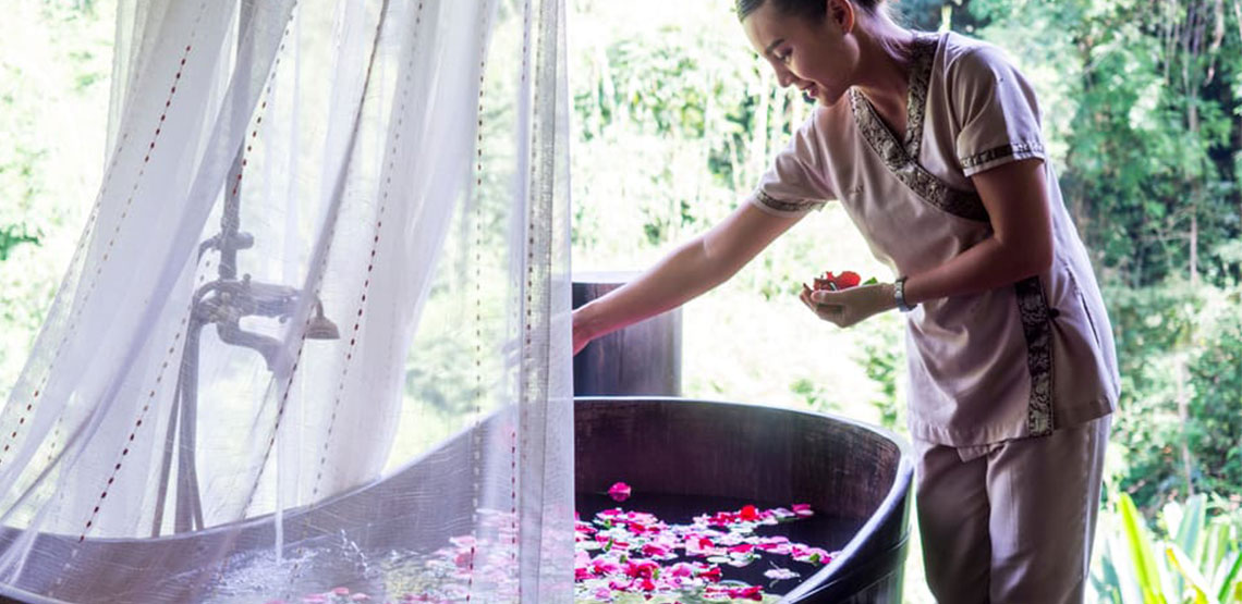 Woman putting flower petals into a bathtub outside