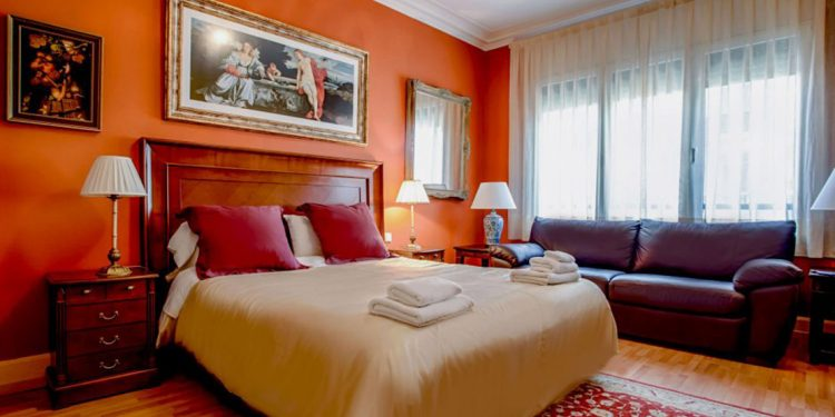 Hotel room with orange walls, leather couch and artwork