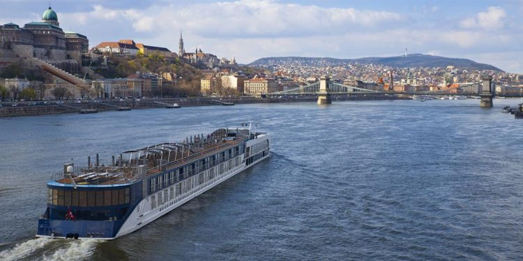 A riverboat cruises on the Danube in Budapest as building-encrusted hills rise before it.