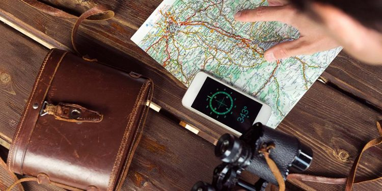 Person pointing at a map with compass open on their phone and binoculars out of case.