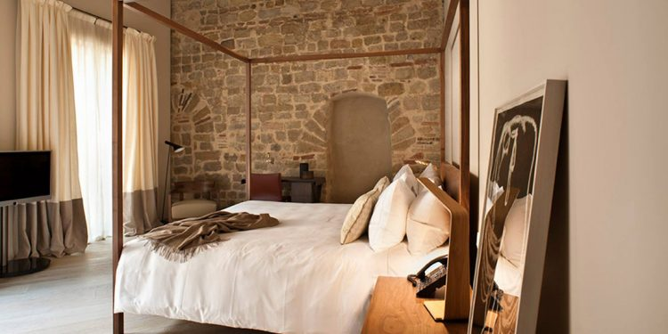 Four poster bed in room with stone wall