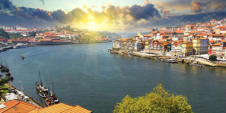 A view of the Douro riverside and Dom Luiz bridge in Porto, Portugal, as the sun sets brilliantly sets off the whitewashed buildings along the shore.
