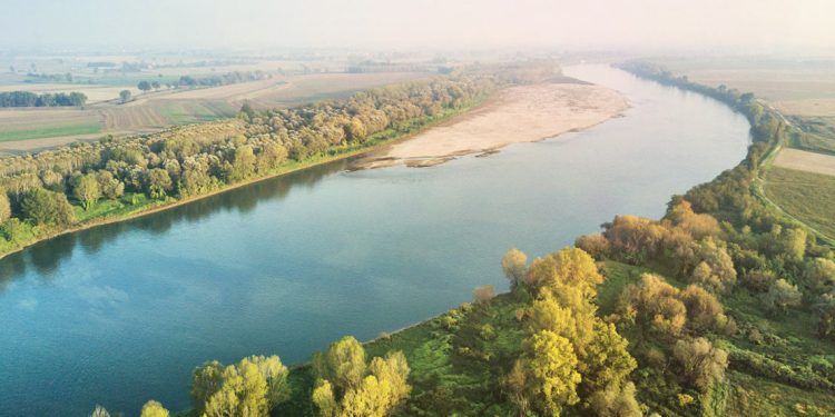 An aerial view of the Po River showing green fields and streets on the banks beside the placid water