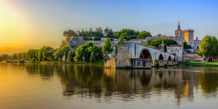 The sunrises over Avignon Bridge and the Pope's Palace in Pont Saint-Benezet, Provence, France, as seen from a river-water view.