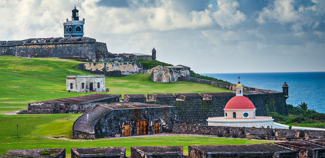 An ocean view from the Castillo San Felipe del Morro, a grassy swath stretching down to the dome-shaped roof of the Capilla del Cementerio Santa María.