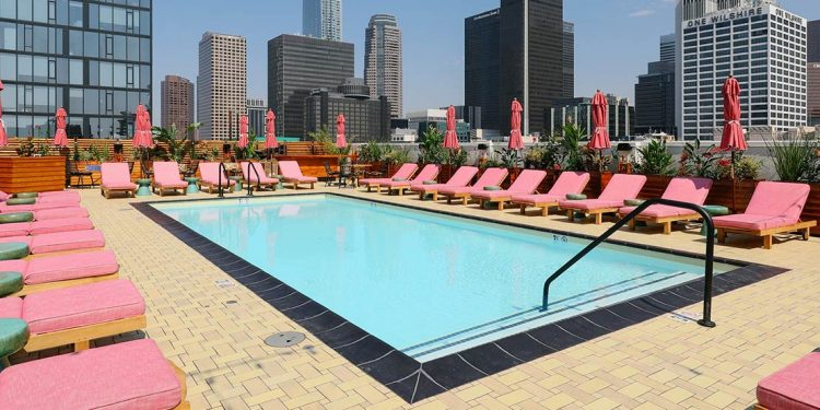 Rooftop pool with pink lounge chairs surrounding and skyscrapers in background