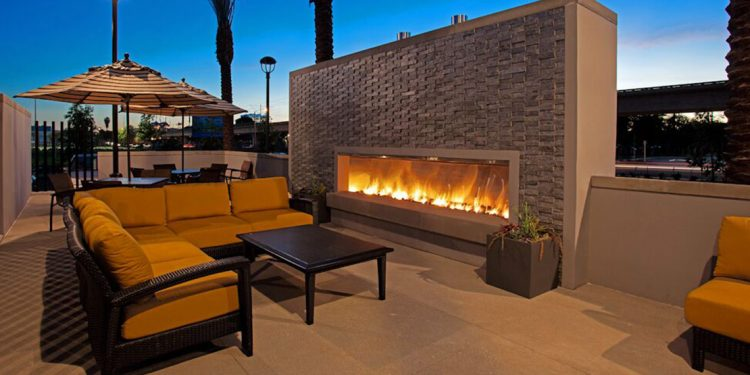 Outdoor fireplace by couch and table