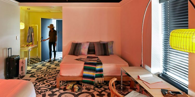 Colorful hotel room with someone walking in the door