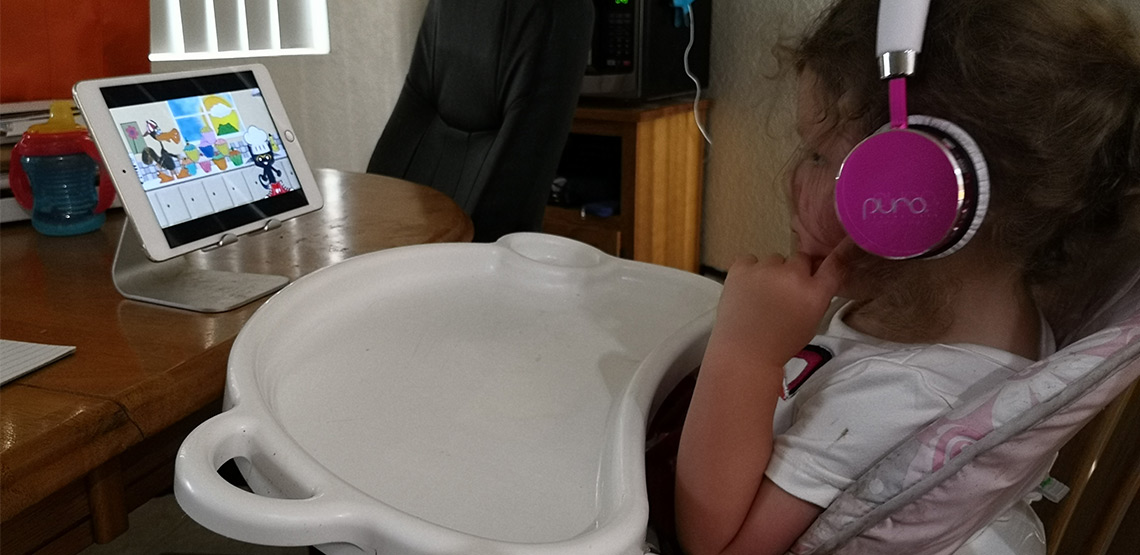 Little girl using headphones and watching show on iPad