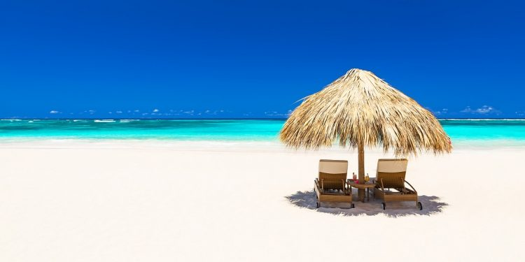 A pair of beach chairs and an umbrella sit on a beautiful, white-sand beach, the deep-blue sky behind them.