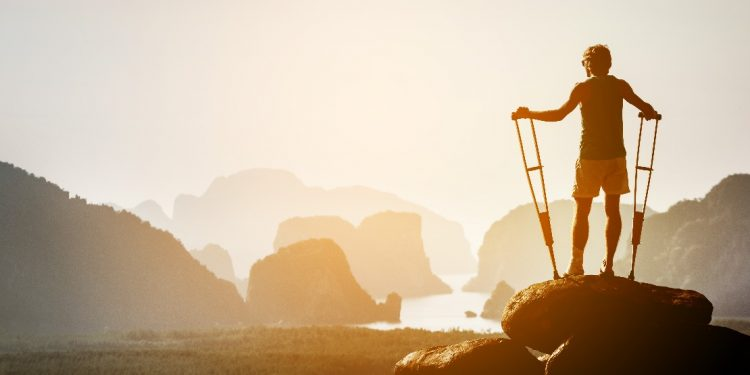 A man holding crutches stands atop of a sun-drenched rock, cliffs rising out of the water in front of him.