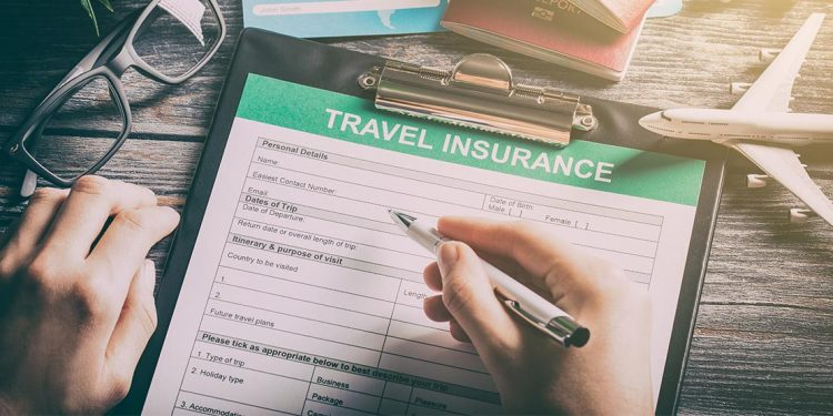 A close up of a travel-insurance application clipped into a clipboard, a pen-holding hand preparing to sign it.