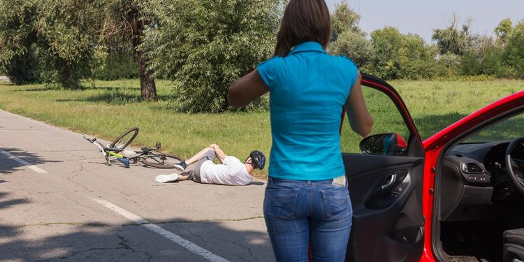 A woman in a blue top stands outside of her car while calling first responders as a cyclist lays on the road clutching his knee.