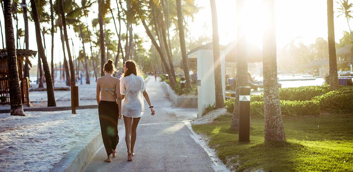 A pair of young women walk side by side on a Dominican Republic resort