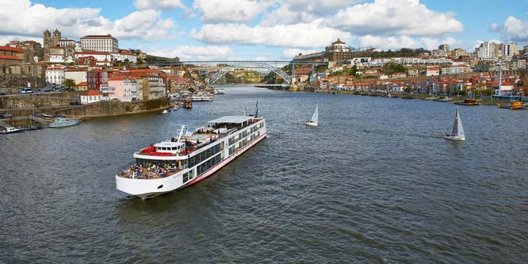 Cruise ship on a river with old buildings along the shore