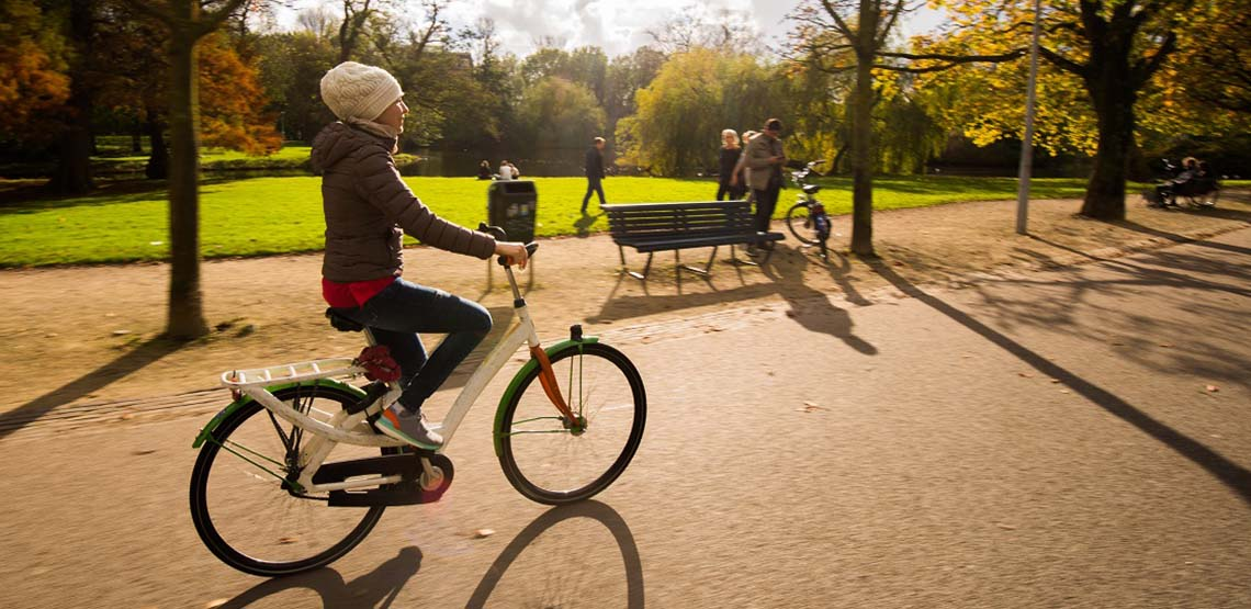 A Girl Rides a Bike in an Amsterdam Park.