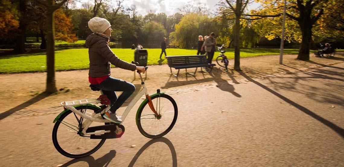 A Girl Rides a Bike in an Amsterdam Park.