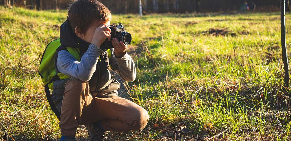 Young boy crouching in a field holding camera to his eye